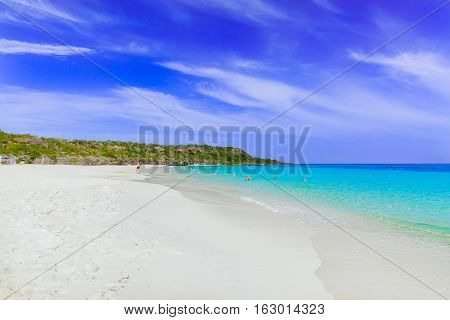 stunning beautiful gorgeous view of tropical white sand beach and ocean against blue sky background on sunny summer day with people relaxing, swimming in background