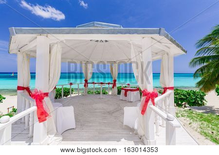 gorgeous amazing inviting view of decorated wedding gazebo at tropical beach on blue sky and tranquil ocean background