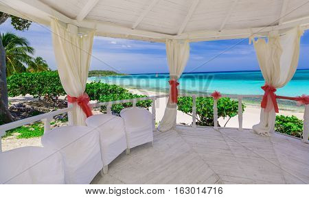 beautiful amazing gorgeous view from the inside of decorated wedding gazebo against tranquil ocean beach and blue sky background