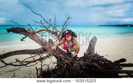 gorgeous amazing funny, angry little girl pirate sitting on old dead tree at the beach against dark dramatic sky and ocean background