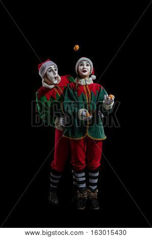 Couple of mimes in New Year costumes posing isolated on black background