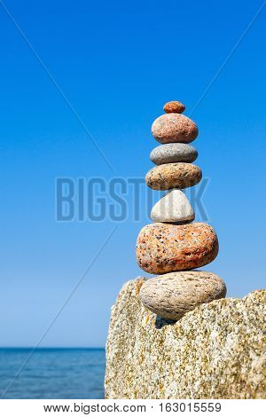 A high pyramid of stones of different colors on the background of sea and blue sky