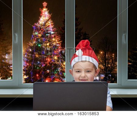Boy looks at a laptop on background of decorated Christmas tree outside the window