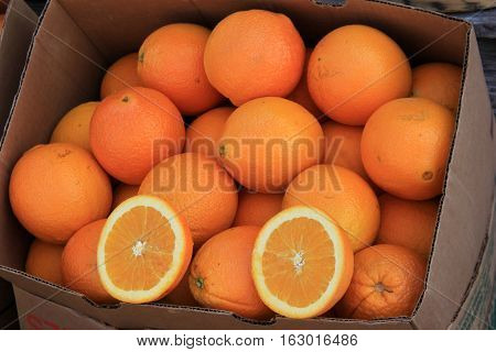 Boxes filled with fresh,juicy oranges, some cut open to show how juicy they are.