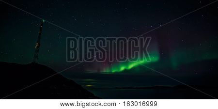 Radio Tower On The Hill And Northern Lights Over The Fjord In The Background