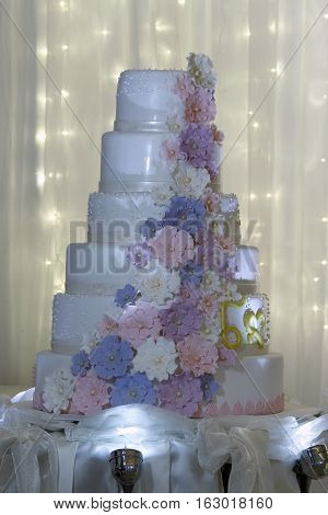Clouse up multi level white wedding cake with pink flowers.