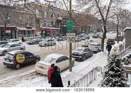 Montreal CA - 17 December 2016: Snowstorm in Montreal. Pedestrians on St-Denis Street.