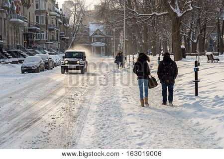 Montreal CA - 17 December 2016: Snowstorm in Montreal. Pedestrians walking near Square Saint-Louis