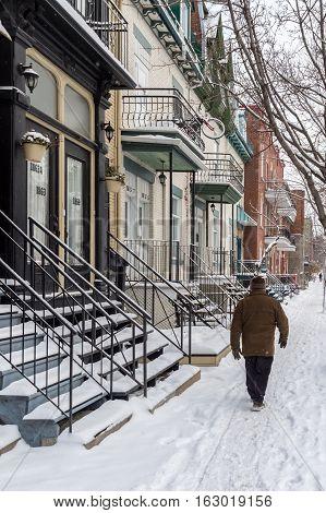 Montreal CA - 17 December 2016: Snowstorm in Montreal. Pedestrian walking on a sidewalk.