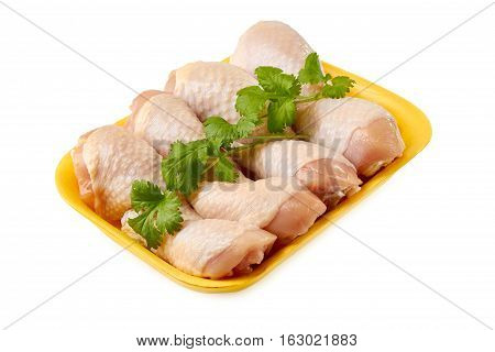 Raw chicken legs on retail tray decrated with parsley isolated on white background.