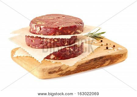 Wooden chopping board with stack of raw beef burger patties and spices isolated on white background