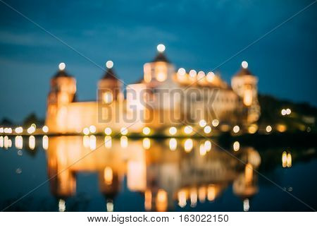 Mir, Belarus. Blurred Boke Bokeh Focus Of Mir Castle Complex In Night Illumination And Reflexions On Lake Water Surface In Warm Yellow Colors.