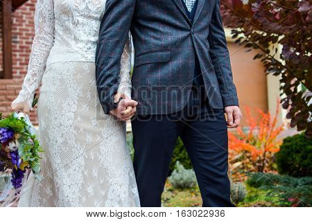 Couple of newlyweds of groom and bride going and looking each other holding hands. In yard around house in autumn season.