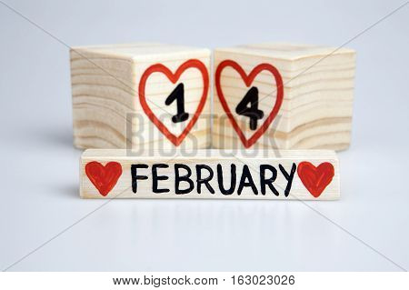 Valentine's day composition with wooden calendar. Handwritten February 14th, red hearts. Bright background.