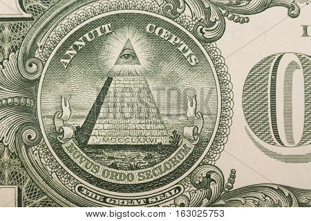 Close up of the pyramid and eye on the back of a one dollar bill.
