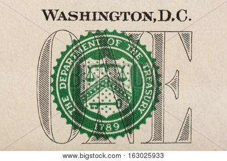 Stamp of the Department of The Treasury on US one dollar bill closeup macro.