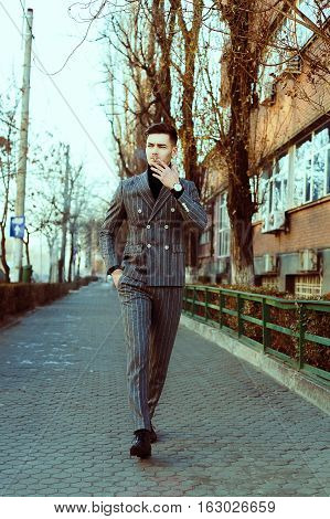 Cool Looking Guy In Fashion Suit Outdoor Smooking