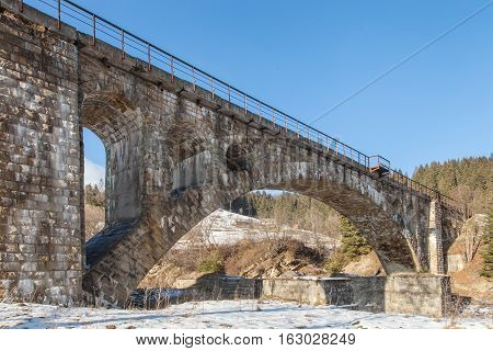 Ancient stone railway bridge the 19th Century in winter Carpathian Mountains Eastern Europe