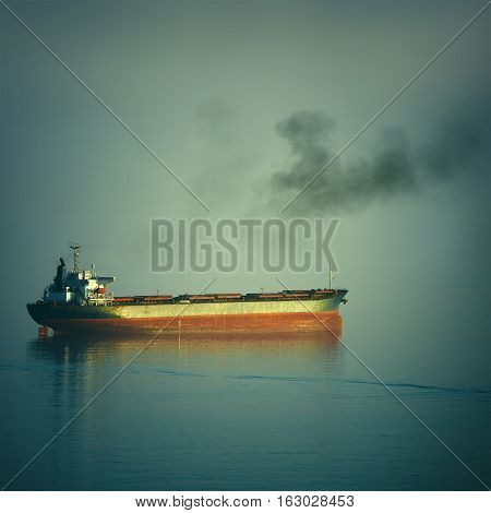 Fuming Bulk Carrier Ship in the Black Sea at the Evening
