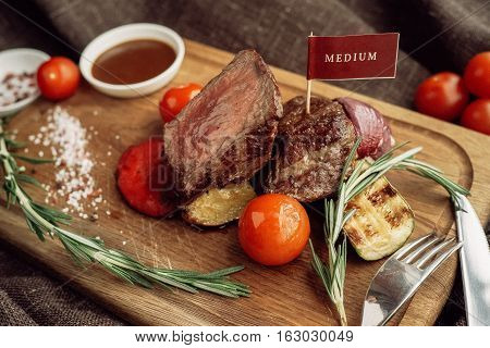 beef meat fillet mignon cutted on wooden plate with fork many different kinds of dry spice over table