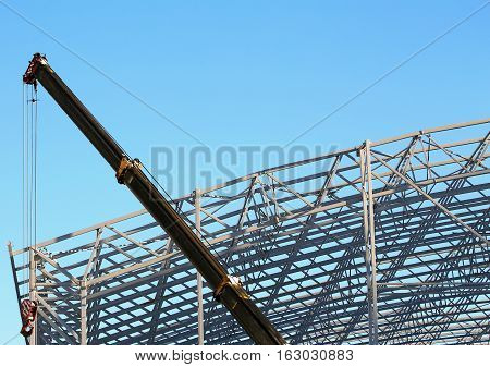 Skeleton of industrial building during construction with crane