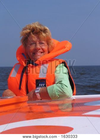 Lady In Orange Against A Blue Sky On A Boattrip