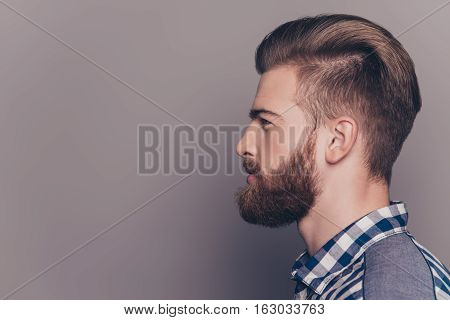 Side View Portrait Of Handsome Thinking Stylish Young Man Looking Away With Copy Spase On Gray Wall