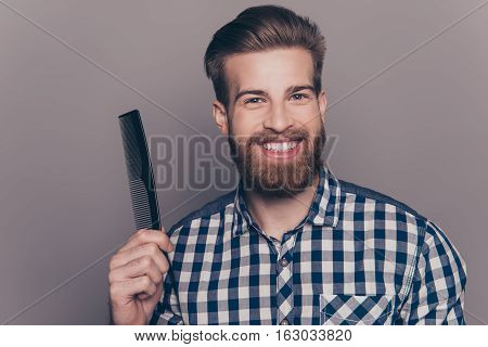 Portrait Of Handsome Cheerful Bearded Young Man Showing His  Black Little Comb