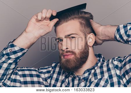 Portrait Of Handsome Cheerful Bearded Young Man Combing His Hair