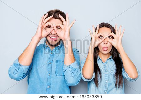 Cheerful Happy Man And Woman Making Glasses With Fingers And Showing Tongue