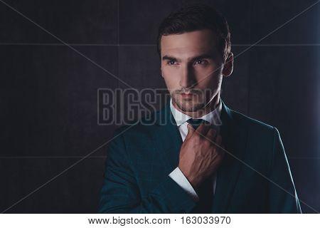 Portrait Of Stylish Man In Black Suit Correcting Tie