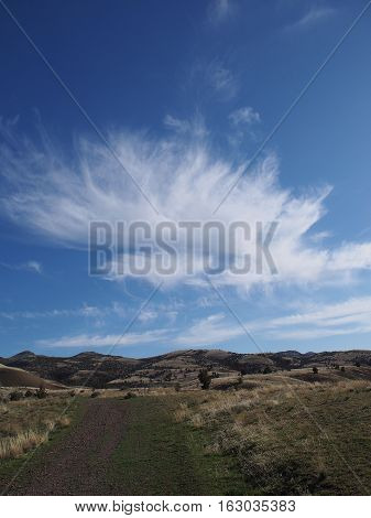 Unique cloud formation over hills and a gravel road in the Painted Hills in Eastern Oregon on a spring day.