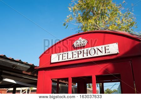 Red telephone booth and mail box in street