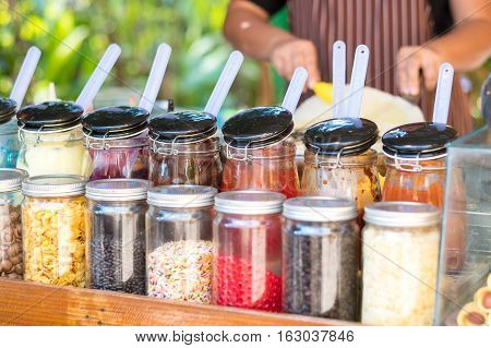 Crape shop with many various topping container. Focus on container with people on background.