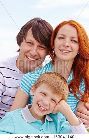 Portrait of cheerful family with son in nature