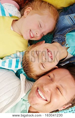 Laughing father laying outdoors on picknic with kids