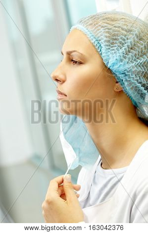 Portrait of a young nurse putting off mask