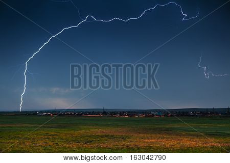 clouds and thunder lightnings and storm. Grren field on foreground