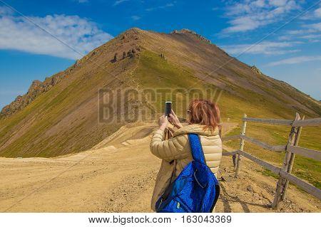 Woman are making photo on her mobile phone at Talgar pass Tien Shan mountains near Shymbulak ski resort Almaty Kazakhstan 2016