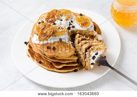 Pancakes with caramelized banana, natural yogurt and chocolate chips. Delicious whole grain pancakes. Healthy breakfast with homemade pancakes