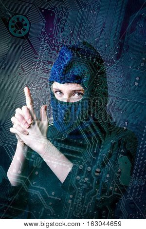 hacker girl in balaclava showing fingers gun on a background silhouette drawing circuit board. concept of computer hacking threats.