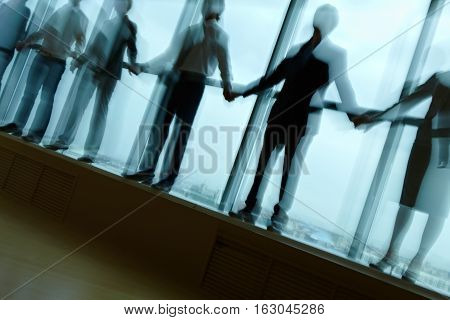 Shadows of office people standing on window sill holding hands in dark office