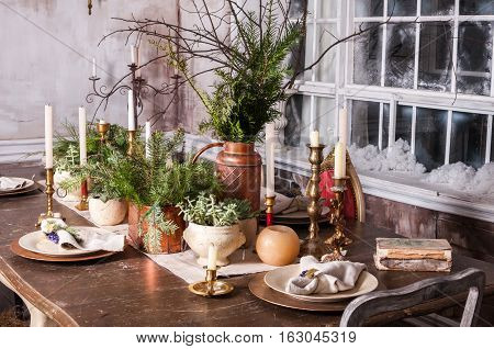 Dining table decorated for Christmas and evergreen centerpiece.