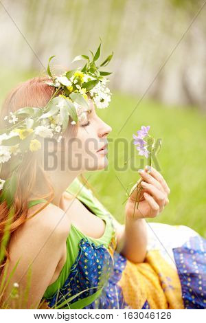 Beautiful woman in wreath enjoying smell of bluebells