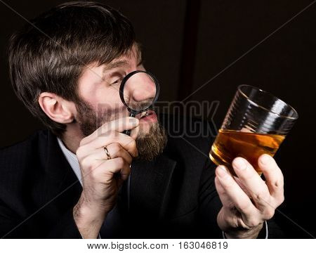 portrait of handsome young businessman looking at brandy through magnifying glass.