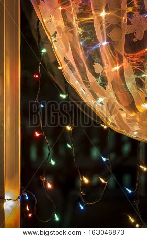 Christmas lights in the window on the background of transparent tulle.