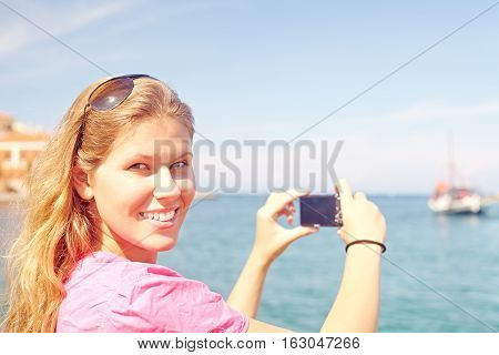 Cheerful woman in travel photographing seascape by sea