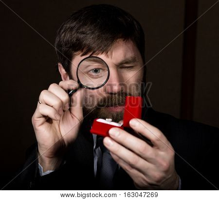 portrait of handsome young businessman looking at precious ring through magnifying glass.