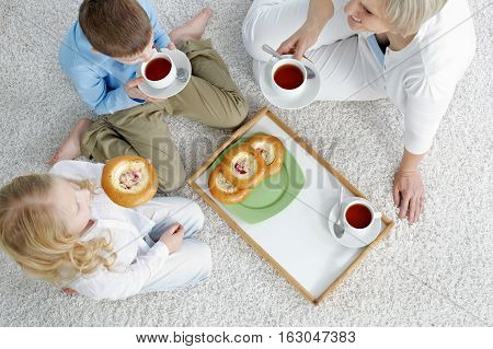 High angle view of grandmother eating buns with her grandchildren