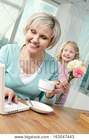 Senior woman using laptop, her little granddaughter stretching flowers behind her back